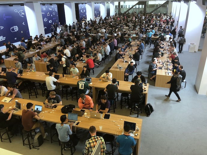 Hundreds of iOS Developers working on laptops at long tables